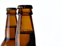 Upper part of two beer bottles. Isolated on white background stock photos