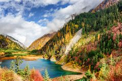 The Upper Seasonal Lake among colorful fall woods and mountains. Fantastic view of the Upper Seasonal Lake with azure water among colorful fall woods and royalty free stock photo