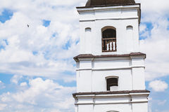 Upper tiers of white stone bell tower. On  background of cloudy sky Royalty Free Stock Photo