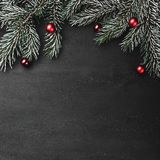 Upper, top, view from above, evergreen branches, tree globes on black square background stock photo