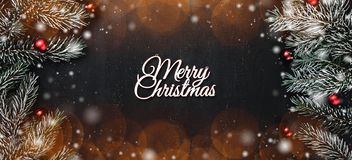 Upper, top, view from above, evergreen branches, tree globes and white Merry Christmas inscription on black background. Snow effect and light beads royalty free stock images