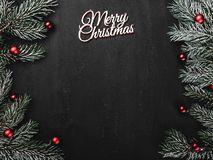 Upper, top, view from above, evergreen branches, tree globes and white Merry Christmas inscription on black background royalty free stock image
