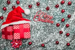 Upper, top, view from above of, evergreen red toys, Christmas presents and Santa hat on gray marble background. With space for text writing, greeting Stock Images