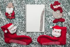 Upper, top, view from above of a notepad, wooden vintage pen, handmade snowman toy and Santa socks on gray marble background Stock Photography