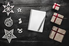 Upper, top, view from above of winter figurines, Christmas presents, notepad and pen on black background Royalty Free Stock Photography