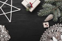 Upper, top view, of Christmas presents on a wooden black rustic background, decorated with handmade star. Stock Photos