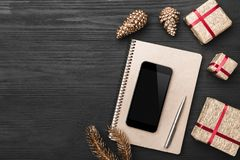 Upper, top view, of Christmas presents on a wooden black rustic background, note pad, pen, phone. Upper, top view, of Christmas presents on a wooden black Royalty Free Stock Image