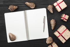 Upper, top view, of Christmas presents on a wooden black rustic background, note pad, pen with space for text. Upper, top view, of Christmas presents on a Stock Photos