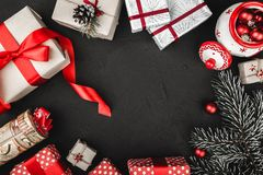 Upper top view of a red ribbon, Christmas presents, tree toys, and evergreen branch on a stone black background. royalty free stock images