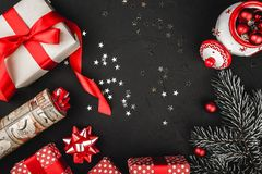 Upper top view of a red ribbon, Christmas presents, tree toys,   and evergreen branch on a stone black background. Stock Image