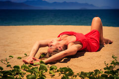 Upper view blond girl in red frock lies on sand bends knee Stock Images