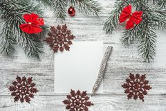 An upper view of a Christmas, new year letter, card writing, on a rustic background, with old style pencil and evergreen. Royalty Free Stock Photography
