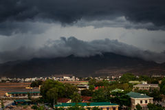 upper view of city dark thunderclouds above city mountains Stock Photography