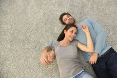 Upper view of couple lying on carpet floor Stock Photos