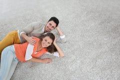 Upper view of couple lying on carpet floor Stock Photos