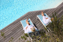 Upper view of couple lying by swimming pool Royalty Free Stock Images