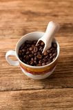 Upper view on cup with coffee grains and wooden spoon Stock Photo