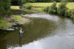 Upper view of fisherman in the river. Upper view of fly-fisherman fishing in river Royalty Free Stock Photos