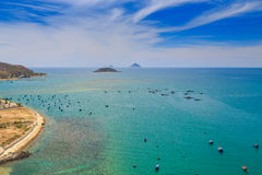 upper view of fishing tourist boats in azure sea by coast beach Stock Photo