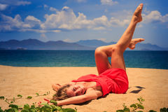 Upper view girl in red lies on sand lifts legs bends knees Royalty Free Stock Photo