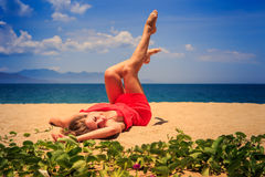 Upper view girl in red lies on sand lifts legs bends knees Stock Images