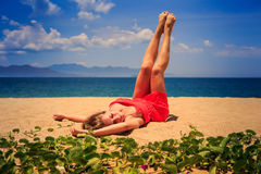 upper view girl in red lies on sand lifts naked legs by creepers Royalty Free Stock Photos