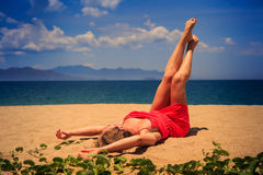 upper view girl in red lies on sand lifts naked legs by creepers Royalty Free Stock Image