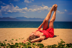 upper view girl in red lies on sand lifts naked legs by creepers Stock Photography
