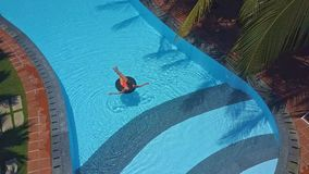 Upper view girl swims on ring in swimming pool. Upper view girl swims on inflatable ring in beautiful swimming pool against palm trees stock footage