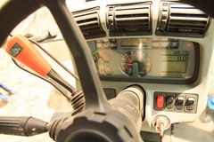 Upper view of instrument panel in tractor cabin through wheel Stock Photos