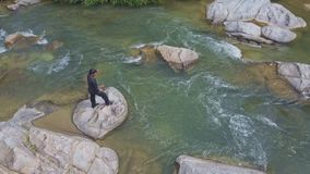 Upper View Man Climbs up River Rock Throws Net into Water stock footage