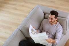Man in sofa reading news Royalty Free Stock Image