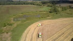 Upper view modern green and white combines gather wheat. Wonderful upper view modern green and white combines gather ripe wheat on field near small stream stock footage