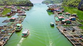 Upper View Motorboats Sail to and Fro near Floating Farms. Upper view tourist motorboats sail to and fro near Asian traditional floating farms against clear sky stock video footage