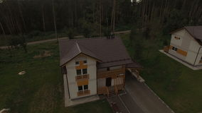 Upper View New Two Storied Cottage in Forest. Camera approaches detached new two storey cottage on village street among pine and fir forest stock footage