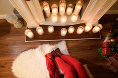 Upper view on a nice fireplace with elegant candles. An upper view on a nice fireplace with elegant candles and two persons` legs in warm socks and bright red stock image