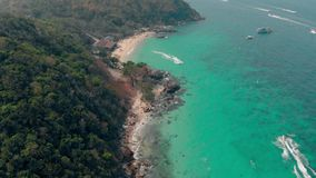 Upper view sand beach and green hills near turquoise ocean. Tremendous sand beach and green hills near turquoise ocean water with speeding motorboats upper view stock video footage