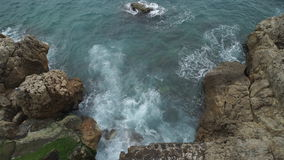 Upper view sea with waves breaking and frothing on a rocky beach. stock footage