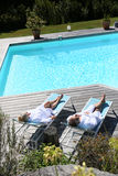 Upper view of senior couple relaxing by the swimming pool Stock Photos