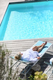 Upper view of senior woman relaxing by pool Royalty Free Stock Photos