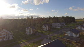 Upper View Shady Streets with Cottages in Evening. Upper panoramic filming of shady street with detached houses in cottage village in evening at sunset stock footage