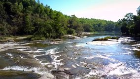 Shallow river with sunshine reflection flows against jungle. Upper view shallow river with sunshine reflection flows against hilly jungle under clear sky stock video footage