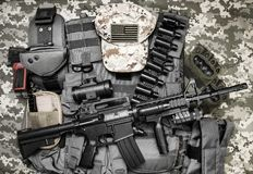 Upper view tactical gear laying on camouflage background. Photo of a tactical vest, rifle, gun, hat with american flag badge and cartrige belt laying on Stock Image
