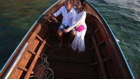 Upper view to bride and groom floating in boat at sunrise stock footage