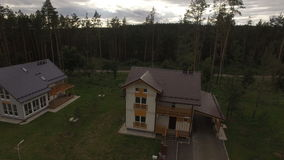 Upper View Two Storied Cottages among Forest. Upper view camera removes from detached new two storey cottage on village street among pine and fir forest stock footage