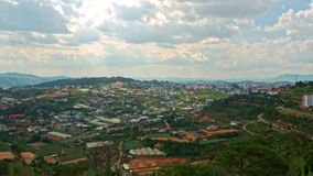 Upper View of Wide Town with Small Houses among Hills. Upper panorama of wide town with small houses among hills against mountains and cloudy sky stock footage