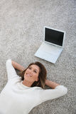 Upper view of woman and laptop on the floor Stock Images