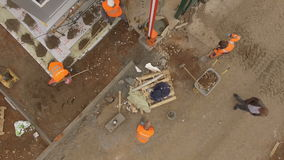 Upper View Workers Dig Hole and Load Ground in Wheelbarrow. KAZAN TATARSTAN/RUSSIA - JUNE 08 2015: Upper view workers in orange jackets dig hole near barrier and stock video footage