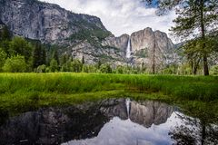 Upper Yosemite Falls and Yosemite Valley. The waterfalls are at full force during the late spring and early summer when snow melt gushes over the granite cliffs royalty free stock image