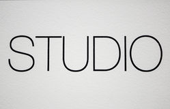 Uppercase word studio. Uppercase word written in white wall studio Royalty Free Stock Image